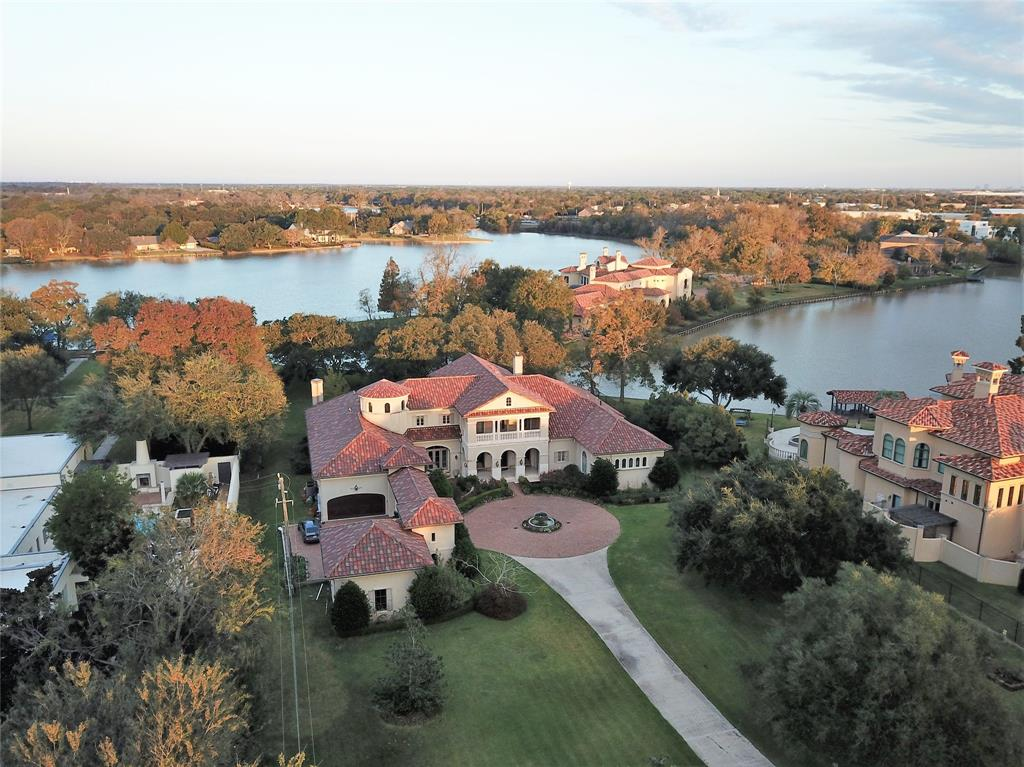 Extraordinary estate on recreational Alkire Lake. Timeless Italian beauty, meticulously designed by Robert Dame, offers the best of town and country living. Only minutes from the cosmopolitan centers of Houston, this bucolic haven, with its forest of trees, gardens, and private dock may even allow for a family farm pet.  The 9226-SF home is perfectly scaled and exquisitely finished. 100' covered terrace lines back perimeter of home, creating a setting for exceptional living & entertainment. Private, serene primary bedroom wing complete with sitting room, workout studio, and spacious, sunlit bath. Secondary bedrooms with en suite baths and terraces overlooking serene landscape and lake. Spacious second-floor rooms allow for secondary owners' suite near elevator and wet bar, media room, game room and more. This elegant, serene retreat, located on a prized, panoramic-view lot, feels worlds away yet is nestled between Highway 90A and I69/US 59, only minutes from Houston's finest districts!