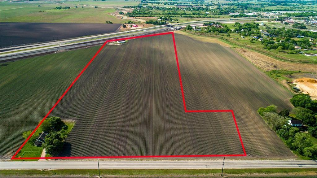 HWY 59 FEEDER ROAD FRONTAGE!!  Investment potential with this 22+/- acre tract with a wood frame home that is currently leased.  Also includes 2424 sq ft building that sits near Hwy 59.  Feeder road just opened along Hwy 59 and there is also frontage along FM 1162.  Perfect for hotel or manufacturing business!!  Water well & septic but is within city limits so city services could be obtained.  The house currently has a tenant and the land is currently being leased to a tenant farmer.  Zoned M-1B.  So much investment potential!