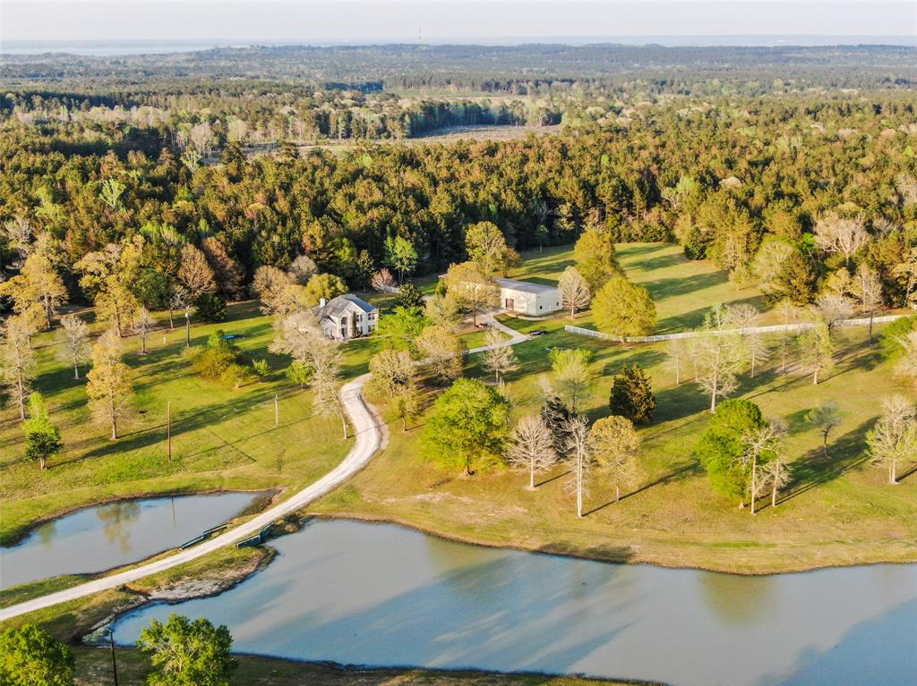 Immaculate 53+ Acre Custom Country Estate in Coldspring, TX 1 hour north of downtown Houston/45 minutes to IAH/Bush Airport. Boasting 4722+ sq. ft. 5BR/4BA, Jenn-Air Pro kitchen appliances, outdoor kitchen/patio with built in wood burning fireplace, 4375 sq. ft. insulated workshop, approx. 7 acre stocked pond w/covered fishing pier & feeder, shooting range, walking trails, fruit tree orchard w/ sprinkler system, raised bed garden & low property taxes with the timber exemption. Additional survey requirements from a lender will be paid for by buyer. Please verify all measurements as there are several sources ranging from San Jacinto County Appraisal District, the original owner's building plans and the sellers whom have added the workshop, an enclosed building for the well and an outdoor shower.  Come hunt, fish, relax and enjoy all the privacy that this estate has to offer.