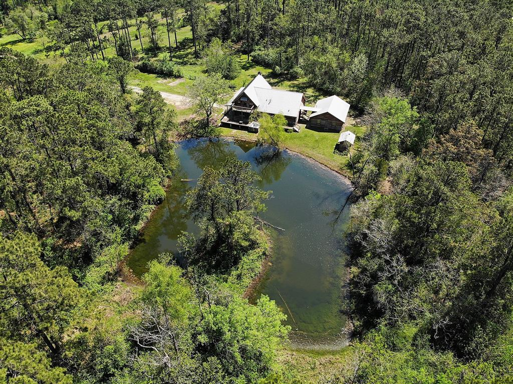 Looking for a little patch of heaven? Here it is! This rare 20 acre property with a log cabin is in the middle of town and waiting for it's new owners. This property has easy access to I-45 but also offers quiet country living. Fall in love with this home as it offers a wrap around porch, large natural pond, stone fireplace in the living room, a loft with balcony, open concept living area, high ceiling in the living room, walk in pantry with sink and large windows. This 3 bedroom 2 bathroom home will make you feel right at home and welcome.