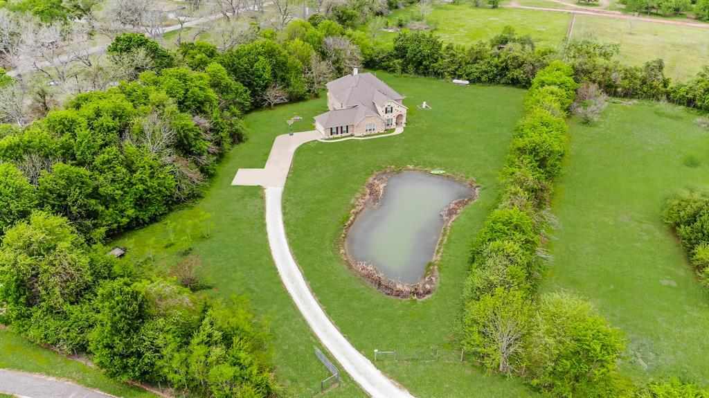 NEVER FLOODED! Gorgeous 2-story, custom home was built so high up that not even Harvey was able to affect it. It checks all the boxes. Sits on 3 acres of unrestricted land. (No HOA) Minutes from the Westpark. Guests are welcomed with it's incredible Stone & Brick elevation and enter onto a two story Foyer with Architectural Archways that make an unbelievable view. Chef's gourmet kitchen w/beautiful granite countertops.  SS appliances include Double Ovens, under Cabinet Warmer, Cooktop & Microwave Oven.  Huge Butler's Pantry, Butler's Bar and Wine Grotto. Kitchen opens to the Extra large Family Room. Luxury Primary Bedroom features its own Private Study, Luxury Bath, his & hers Closets, Double Sinks.  Upstairs is just as amazing with Oversize Bedrooms, Game Room & Media Room. Other features: Full home water filtration system, 2 different areas for washer/dryer hook up, 4-car tandem garage. Enjoy the afternoons fishing in your very own stocked pond or relaxing on the oversized Balcony.