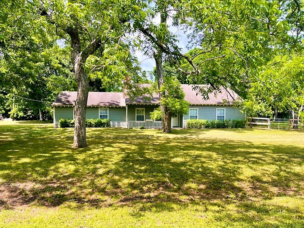 Move WEST and enjoy the country living, in a quiet community, 15 minutes from major shopping and  major thoroughfares.  All tile flooring, easy to maintain, stacked rock, wood burning fireplace, mature trees and a sunroom full of window closed in with AC and Heat, this will be your favorite room!  3 bedrooms, 2 full baths, easy to maintain home with new hardi-board siding.  Sit out on the front porch and wait for the kids to come home from school.  Fenced in back yard that backs to a green belt, Old Country Club.  LCISD schools in Fulshear.  Great equestrian community, on a quiet street.  Find your peace and comfort here.  Home is on a water well and septic system, so NO MUD taxes.  Need 24 hour notice for showings, tenant is still on property till the end of April.