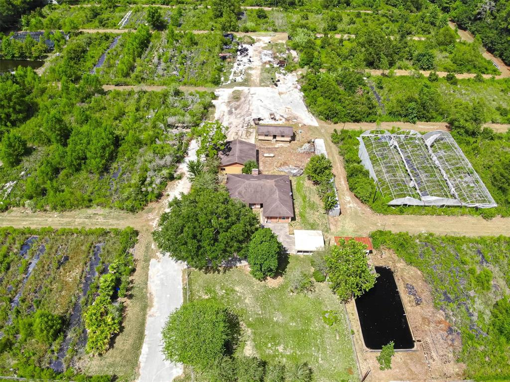 Leave the city life behind and start living your best life on an unrestricted 12.91-acre farm complete with a home, office, 2 wells, two ponds, greenhouses and 150+ 100-foot irrigated rows for farming whatever your heart desires.  This unrestricted property located on the furthest point in Harris County outside of the city limits is located right near the next phase of The Grand Parkway and minutes to Hwy. 59.  This property features 4 bedroom and 2 baths.  Property is fully fenced and located in a quiet section of Huffman.  The property was originally used as a tree farm and everything still works.  Opportunities abound on this unique property.  Room sizes are approximate.