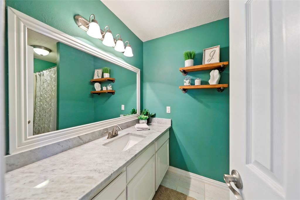 Updated full bath in hall includes tub/shower combo and modern industrial shelving.