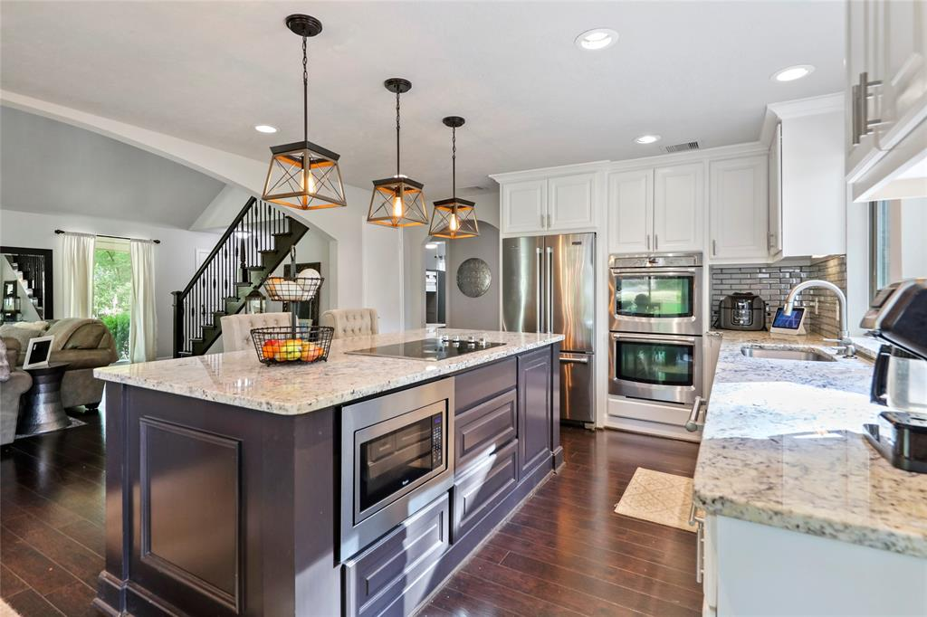 Glam kitchen features granite counters, stainless appliances, double ovens, built in microwave. (Matching refrigerator can stay if desired!)