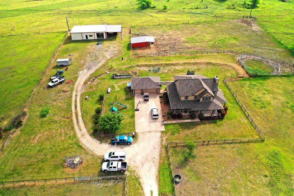 Houston Hill Country at its Finest.  Horse ranchers dream.  Cross fenced with small three stall barn and feed storage area.  60' x 40' shop with TAC Room and Studio Apartment inside the shop both climate controlled with septic tied in, 30' covered extension for Tractors and Equipment.  Beautiful and minutes North of the new 249 extension.  Main home is perfect for a Family, Master and all common areas down.  The raised bed garden is already started and producing.  Small Clusters of trees blocking view of the Home from CR 405.  This home even has High Speed Internet and utilities run from the back of the property.  Wrap around porch on three sides of the home, and private entrance into the Master Suite.  Extremely Rare property with all the additional value Included.