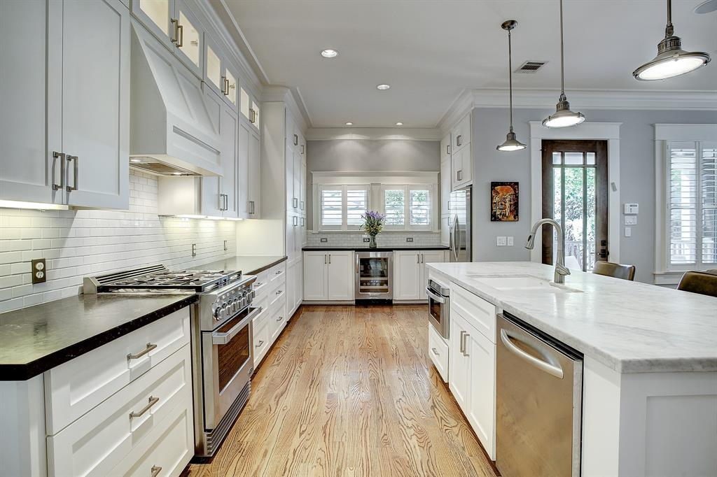 This kitchen is huge, with an insane amount of cabinet and counter space. The dark countertops are granite, the white island is marble. The appliances all transfer with a sale, including the wine fridge at the far end.