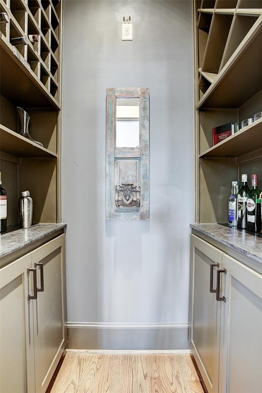 The wine room behind the glass door in the family room has lower cabinets on both sides, and storage for approximately 120 bottles of wine above (buyer to verify).