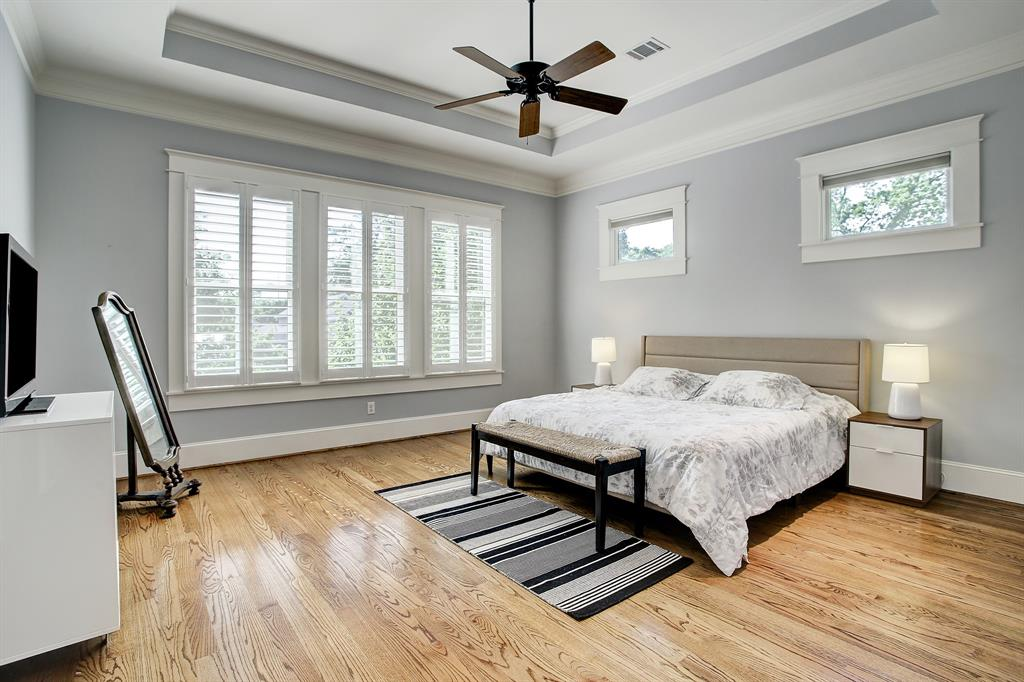 The massive primary suite sits at the back of the home and overlooks the back yard and pool (this is a king size bed). Note the architectural tray ceiling and plantation shutters as elsewhere throughout the property. The windows above the bed have cordless blinds currently in the