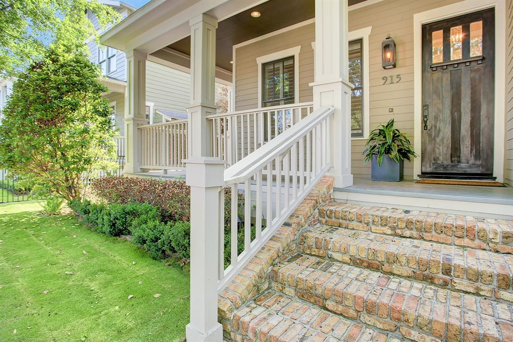 The fully fenced front yard provides grassy play or lounge space, as well as a covered front porch and wide staircase leading to the front door.