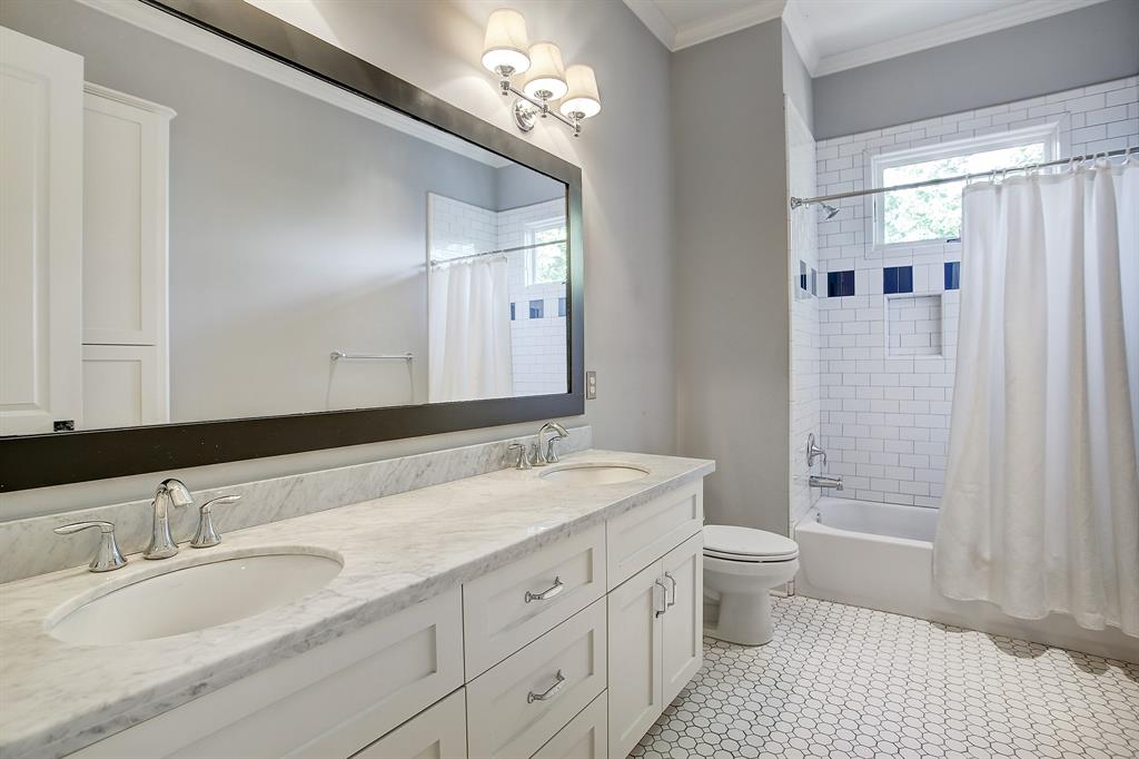 The full bath shared by the secondary bedrooms is also beautifully finished, and is very spacious with a double bowl vanity and linen space (behind the door in this photo).