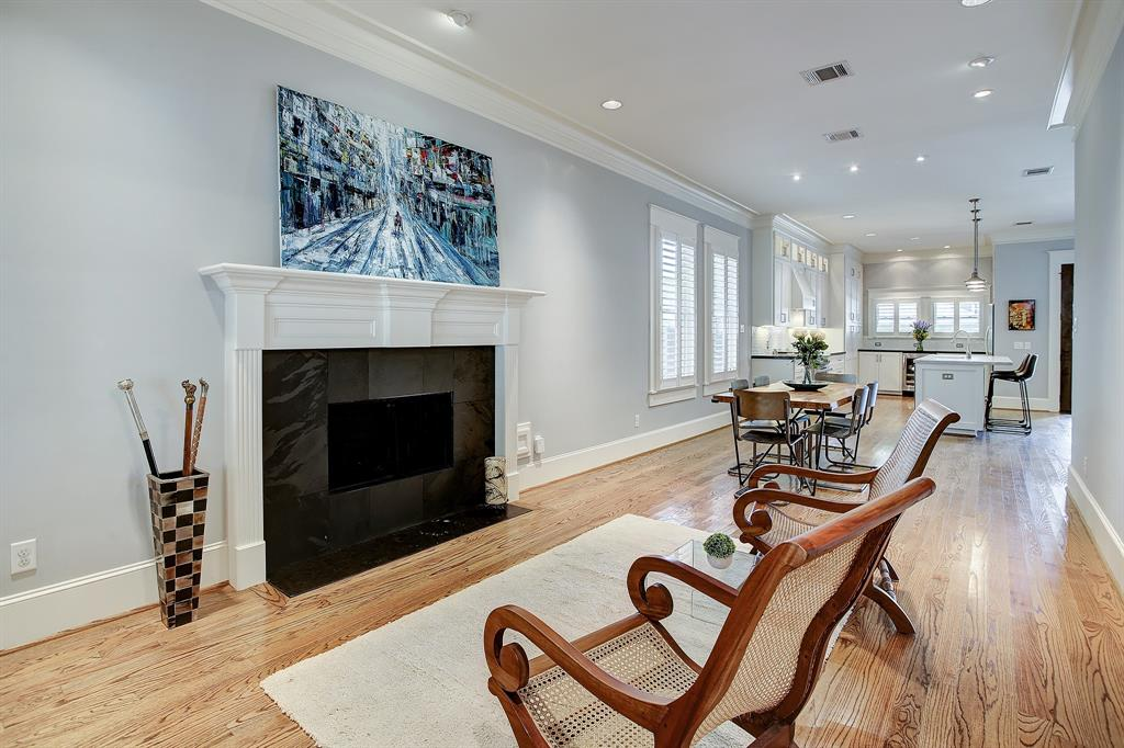 Across from the study/office is a formal living area with a gas log fireplace that extends gracefully toward the dining space, kitchen and family room.
