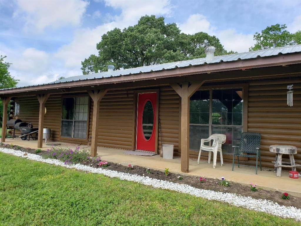Log Home on 4 acres plenty of room for horses.  Rolling topography, garden space and a lot of open acreage. 2 Bedrooms 2 baths with open floor plan from kitchen to den. Wood burning fireplace. Large  primary bedroom and bath. Survey provided. Country setting with front and back porches.