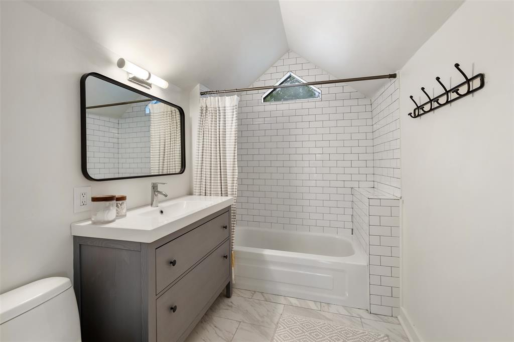 This master en suite was updated with a new vanity, stone flooring, and a gorgeous subway tile shower surround.