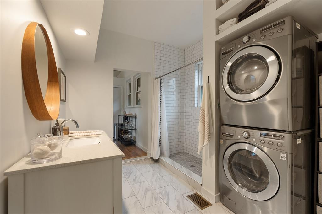 Located just off the guest bedroom, you will find this renovated bathroom. The bathroom has been updated with stone flooring, subway tile shower surround, and beautiful penny tiles on the shower floor. Per the seller, the downstairs bathroom shower was replaced in 2020.