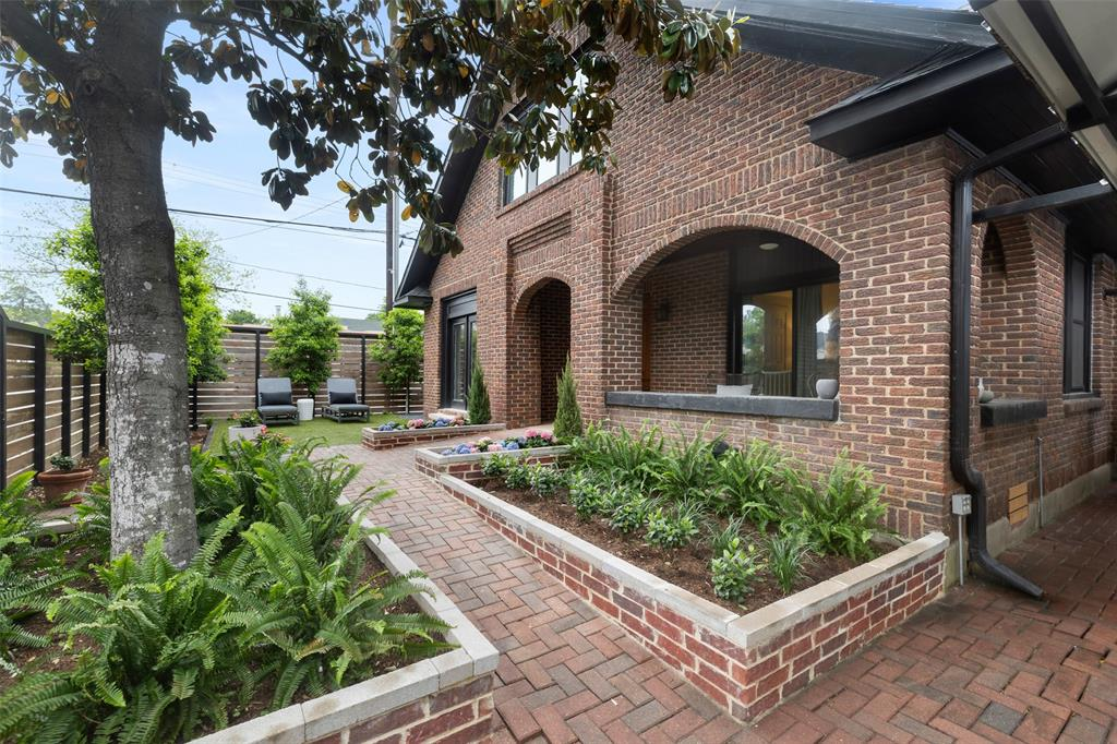 This fully fenced property includes this gorgeously landscaped courtyard, which includes a beautiful, mature magnolia tree, brick paver walkways, and elevated planters.