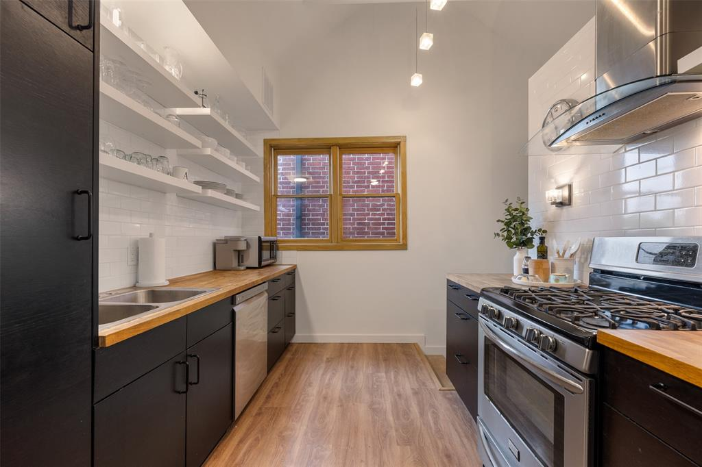 Home chefs are going to love this kitchen with its butcher block countertops, open shelves, reach-in pantry, and gas range. Also, notice the gorgeous window casing. Per the seller, windows were replaced in 2019.