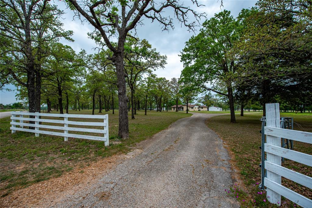 Large brick home (2416 SF) situated on 3 unrestricted, fully fenced acres in a quiet area of Giddings. Numerous mature oak and pecan trees create a relaxing country setting. 3 bedrooms, 2 full baths with half bath off of the inside utility room. Two car tandem attached garage has been converted for extra living space with an additional half bath (two toilets and sink-space could be reconfigured to a shower to make a third full bath). Private space for guests, bonus room, workshop or a nice garage. Space also includes a kitchenette (stove may be excluded per seller). The main kitchen is open to den which has a wood burning fireplace, built-in shelves and large windows. Nice size pantry with counter space as well as a breakfast nook that overlooks a courtyard. There is also an office/hobby room and formal dining room, living room or office. Several walk in closets throughout the home. Outside has two additional buildings with concrete slabs, electricity and built in storage.