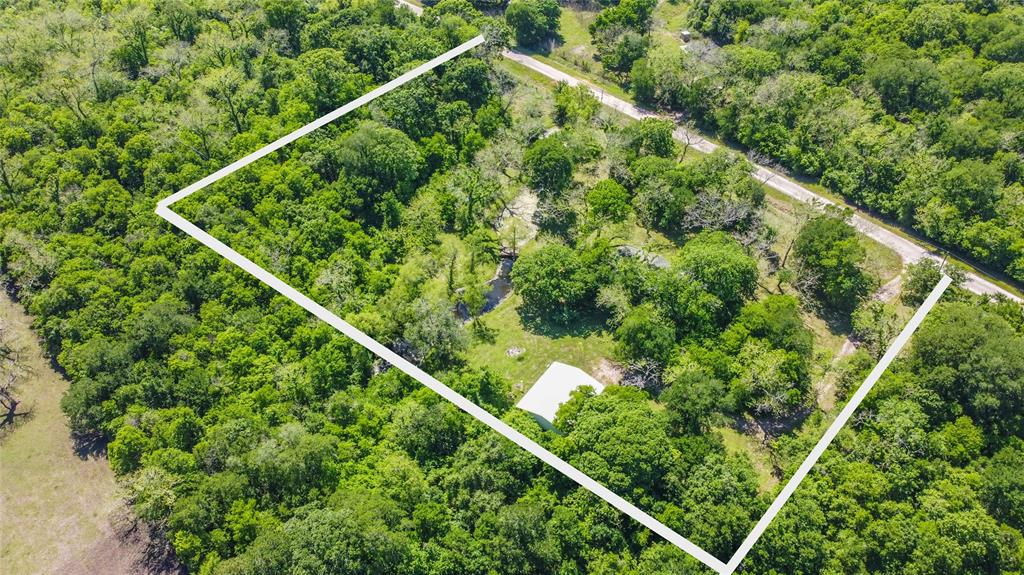 10.47 acres of country living with tons of potential! Mix of mature woods, pecan/oak/pine trees and open space with a pond located off a quiet dead end county road * per seller.  Water well, septic system, electricity and propane tank available and onsite. On the property sits a 4 bedroom 2 bathroom doublewide mobile home manufactured in 1994 and built in 2005 a 46x26 workshop on slab with rolling door and carport.  Property is being sold for Land value and any structures/systems on site are being sold as is where is.