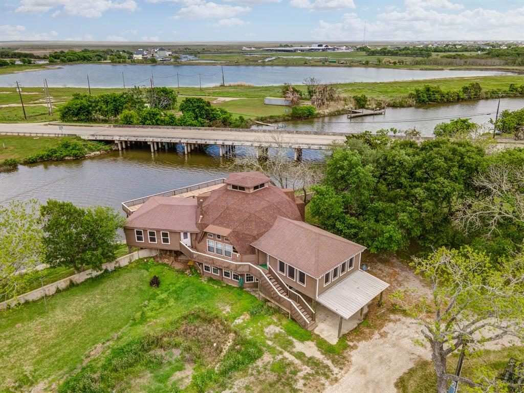 Be amazed by this impeccable 3-bed, 3-bath waterfront home in Oyster Creek, which boasts high ceilings, wood flooring, stone-surround fireplace, ample natural light, recently replaced roof, new HVACs on 2nd and 3rd floors, ground floor service lift, stair climber, 2 kitchens, and oversized bedrooms, bathrooms, den, and game room. The levy protected home features a long wood deck overlooking the beautiful Oyster Creek, 2 boat docks, fishing deck, storage shed, abundant green space, and a covered patio. The island kitchen is complete with expansive quartz countertops, tile backsplash, gas cooktop, wine cooler and wine rack, stainless steel appliances, glass-fronted cabinets, breakfast bar, and 3 pantries. The spa-like primary suite includes a walk-in closet, dual vanities with knee space, and a large shower. The Gulf and Surfside area are only 3 miles by boat and 5 miles by car. Multiple nature parks, grocery stores, and restaurants are only minutes away!