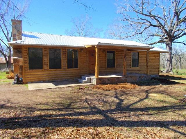 Great location located on FM 323 about half a mile off Hwy 84 East. This 2 bedroom 2 bath newly built home was finished in late 2020 with almost 1,300 square feet. It features an open concept floor plan with a beautiful kitchen that has lots of cabinets and comes equipped with new stainless- steel appliances. Some of the features you will love are the solid wood doors throughout, the nice flooring throughout, the electric insert stone fireplace, lots of windows for natural light and the unique Texas start built in the ceiling in the dining area. The main bedroom is spacious with an on-suite that features a shower/tub combo. Outside you will find a nice covered front and back porch. The property is 8+/- acres of beautiful, cleared land that offers a buyer ample opportunity for usage, a metal building on a slab with over 2,000 square feet and rollup doors. This property has three driveways, three water taps plus an extra slab. The property would be perfect for business and residential.