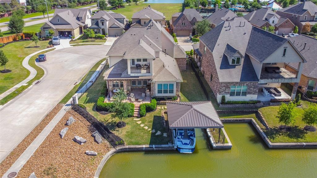 Magnificent waterfront home on a corner in The Waterway w/backyard paradise: covered boat house w/bumpers, side yard ready for a pool, outdoor kitchen w/pellet grill/2burners/sink, stone firepit & covered patio. Rare 5 bed/4 bath has soaring entry w/hardwood floors, custom paint & plantation shutters throughout. Formal Dining & Gourmet Kitchen w/granite island, glazed subway tile backsplash in herringbone pattern & designer cabinets w/SS hardware. Living Room w/fireplace & shiplap accent wall, floor to ceiling wall of windows w/lake views. Exquisite Master Suite w/wood accent wall, window seat in bay window & spacious bath w/tub & step in shower.  Guest Suite w/full bath downstairs & quaint seating area leads to winding stairs to 3 Bed/2Baths (1 currently being used as an office) plus Game Room w/balcony overlooking lake & tiered Media Room.  Epoxy floored 3 car garage w/storage, sprinklers, termite protection system, landscape lighting & full gutters. Lake life at its best!