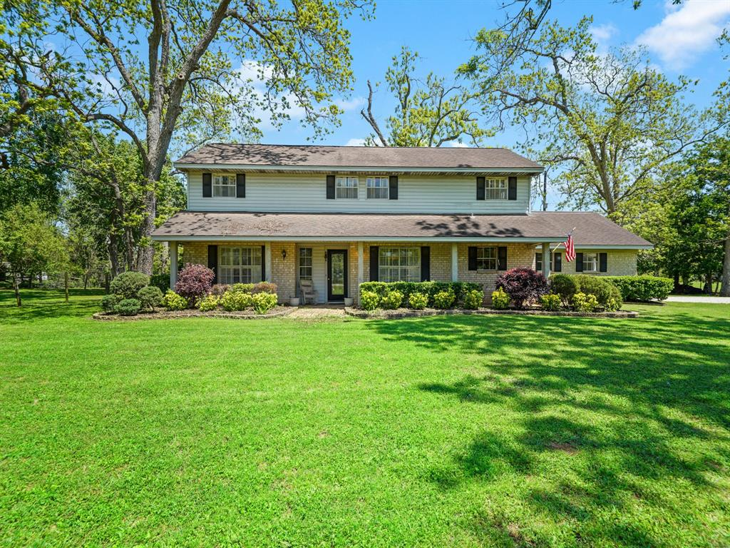 This lovely home sits on 6 beautiful secluded acres in Fulshear in a neighborhood that is a hidden gem.  The lush property is covered with mature Pecan trees and is already fenced; perfect for raising children, riding horses or peaceful evening strolls.  From the large great room and patio area the view is of enormous Pecan trees and a lake that is not only home to ducks year round, but visited by heron and other bird species throughout the year.  The home's large primary bedroom is on the main level and there are 3 oversized bedrooms on the 2nd level.  The main barn has 3 large stalls (two are 12X24 and one 12X12) and a wash rack is move in ready!  The second barn sits on the opposite side of the property perfect for separating horses or cows if needed.  Don't miss this house if you are looking for your own private oasis outside of Houston. Per seller Home has never flooded.