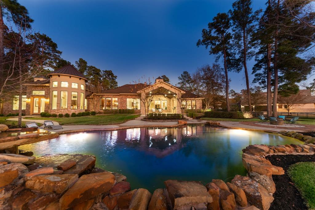 """Come home & escape reality at this glamorous lakefront estate boasting 242 feet of waterfront views! You can have it all- lifestyle, luxury, & location! This custom home was designed for relaxation & entertaining! PRIVATE outdoor oasis elegantly lights up the custom landscaping at night & offers 400+SF of covered patio space, outdoor kitchen, fire pit, & heated pool. Open floor plan is flexible w/convenient 1-story living w/wide hallways & door frames. Impressive kitchen w/stainless appliances, ice maker, warming drawer, & 42"""" GE Monogram Fridge. Downstairs designer media room & enormous game room offering both a dry & wet bar make entertaining a breeze. Additional features include: Private guest casita, home security system, surround sound, spray foam insulation, generator, & upstairs bonus space. Come see what the hype is all about! Own your own piece of heaven w/convenient access to Houston, The Woodlands, & IAH! Zoned to top Conroe ISD schools - it's what you've been waiting for!"""