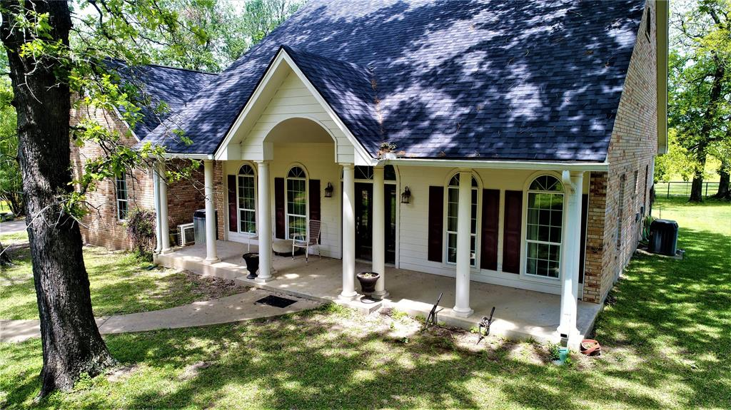 This gorgeous 4/3 brick home surrounded by towering oak trees sit on an 100-acre cattle/horse ranch with improved coastal hay meadows, 5 stocked ponds, and White Rock Creek meanders through the property. The pretty entryway opens to a formal dining room. The living area has a wood-burning fireplace with blowers and a wall of windows across the back of the home that overlooks pretty pastureland. The kitchen is complete with granite counter-tops, custom cabinets, nice appliances, and a breakfast area. The spacious master suite has walk-in closets, his and her sinks, oversized jetted tub, and a separate shower. One guest bedroom has access to a hall bath that will serve your guests well. Two additional guest bedrooms across the home share a hall bath. Outdoors, you will find: 40'x80' shop, 30'x80' shop, 20'x100' equipment shed, 65'x100' equipment shed, 50'x60' RV shed with 50 amp breaker, 3-car carport, 50'x60' hay barn, 2 grain silos, 700' deep water well and sprinkler system.  Come see!