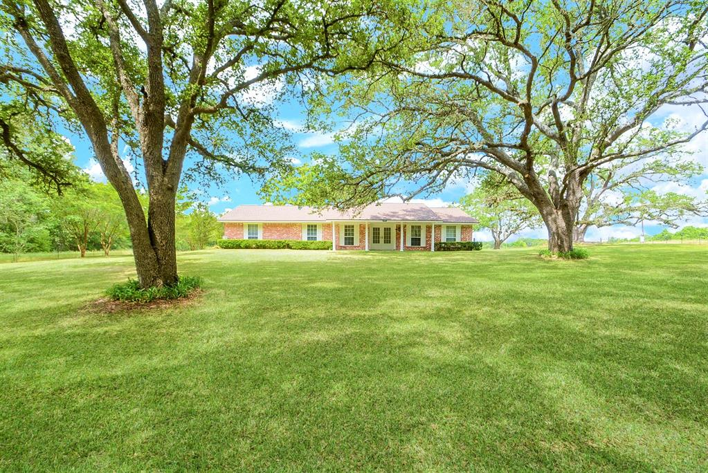 """11 Beautiful Acres setting with massive live oaks, views  and backs to exotic deer ranch. Lovely 1-story brick home with spacious rooms, 3 bedrooms, office, 2 full baths, lots of closet space, formal dining room, covered breezeway/patio to  2 car garage & 2 car carport in back PLUS 24'x30' Metal Shop Bldg. Notes:  """"Lifetime"""" Roof replaced in 2020, 5-ton Trane 19.5 Seer HVAC replaced in 2019, Septic replaced in 2015, double pane windows, brick wood burning fireplace, kitchen updated with granite, custom cabinets, 5 burner electric range top, 2 ovens, refrigerator, dishwasher, microwave, walk in pantry.  Raised beamed ceiling in den.  Primary bedroom with sitting room, 2 walk in closets, double vanity, walk in shower.  Hall bath with whirlpool tub with shower.  2 security cameras that work off a phone app., nice laundry room with cabinets. TVs stay with house. Hog Panel fencing around yard area, gated entrance off Sommer Lane ~ very quiet to stargaze at night.  Very private."""