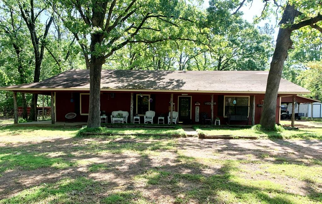 This beautiful country home on 12 acres is located just off FM 2160, north of Crockett, TX. The asphalt country road leads you to the pipe entrance. There are nice, large porches on two sides of the home, and a wooden patio area on the back, near the carport. Through the back door and to the left, the kitchen looks out over the dining area and large living room. The master has a huge walk-in closet with center island/shelving and an additional door into the master bath. Through the secondary bedroom, there is a room that is currently being used for storage, but it could also be a cute little sitting area, office, etc. There are many unique, rustic touches to this home that make it stand out. Multiple fruit trees (mostly pears and peaches) add to the beauty of this peaceful setting. There are many outbuildings and barns in place, allowing for tons of storage space and room for your animals! This property is fully fenced/cross fenced and has multiple pastures, one with a pond.