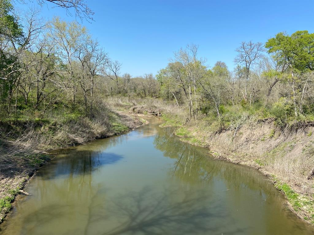 Approx 11 acres on beautiful live water Mill Creek located a short distance from the historic square in Bellville. Easy commute to I-10. Features sandy soil, electric in place, scattered trees and nice wooded habitat for wildlife along the creek. Ideal spot for homesite. In Bellville ISD. New homes being built in the area, nice neighborhood. Great hard to find medium size tract with convenient location. Enjoy this pretty live water property. List price $25,900 acre. Seller to keep all owned minerals and waive surface rights. Buyer to verify Ag Exemption for future use.