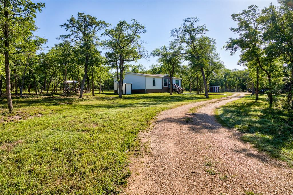 Nestled in the heart of Burleson County is this beautiful 5.56 acre park like property.   Built in 2019 the Clayton Homes residence features 3 bedrooms, 2 baths and 1456 of open living space.  The home is all electric and ALL appliances will stay, including the stand-up freezer in the utility room.  Other amenities include: - 2.5 acres of wooded trails  - Chicken coop - 30x50 full barn dimensions   *18x50 for RV and 12x25 shop - 18x50 RV area with 50 amp service and sewer hookup - 200 amp power to the barn  - water supply to the shop with additional washer and dryer hookups.   - Ionized water well filter - Reverse osmosis filter in the home   This beautiful property backs up to the Triple J wildlife ranch.  Many days you can see the most beautiful exotic animals from the back porch!