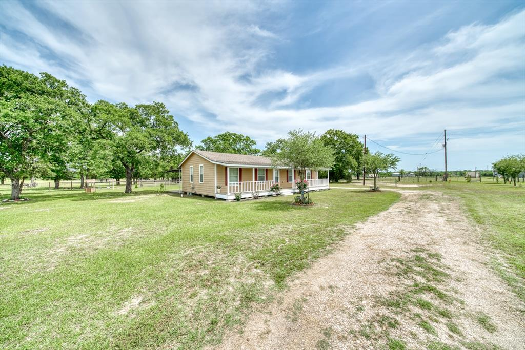 Your search for a farmhouse on a few acres ends here at Country Town Estates. Your new Texas rural mini ranch is located just 30 minutes from Huntsville and 45 minutes from Bryan/College Station.  The updated Hardiplank home features a split plan, 3 bedrooms, 2 full bathrooms, open concept kitchen/dining/living areas, long front porch, and covered outdoor patio ready for entertaining guests.  The park-like property has a gated entrance, a 30x40 barn, livestock shed, pond, fence, and cross-fence.  This rural property offers the opportunity to be your full time residence or a weekend retreat.