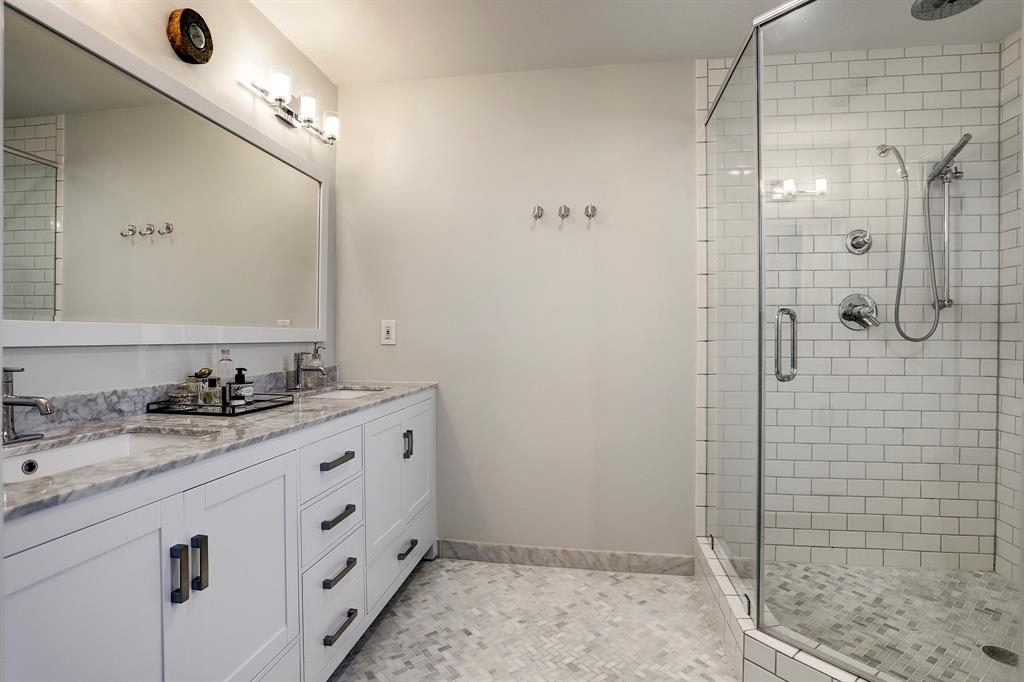 Updated primary bathroom with full sized shower, granite counters and beautiful white finishes.