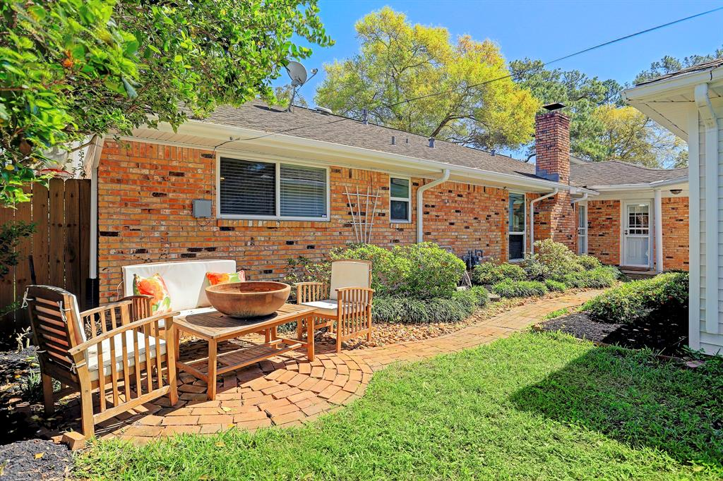 Backyard features brick paver patio and green grassed area.