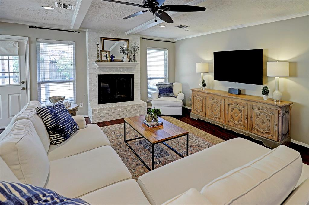 Open living room, wood floors, fireplace, and plenty of natural light!