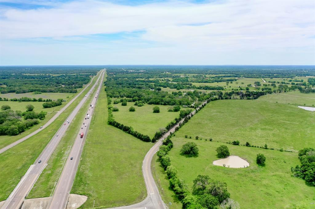 21+/- Acres Highly Visible from I-45 with access off Spur 104. This property is a diamond in the rough ready for commercial or residential development. Located in Southern Madison County, it is near the Projected TXDOT Loop also know as the SH 21 relief route. This projected loop proposes to connect regional traffic in the Madisonville area, which will relieve SH 21 (Main Street) and surrounding roadways from through traffic between I-45, SH 75, SH 90 and SH 21 (per TXDOT website). Presenting approximately 70% open/ 30% wooded with a nice mix of hard and soft woods and sloped terrain.  This property offers quick access to I-45; and is located between Dallas and Houston.
