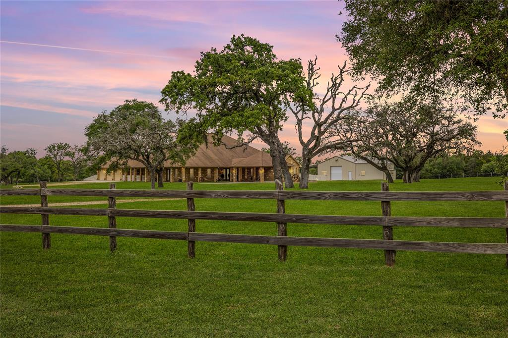 Enjoy this luxury South Texas ranch home on 100 acres just outside of charming Hallettsville. Within a short distance from major metros, this is an ideal property for anyone looking for a quick getaway, corporate retreat, hunting camp or full-time residence. The home boasts 4 bedrooms and 3 full baths, chefs' kitchen with commercial grade appliances, open concept living with formal dining room, breakfast area, office and a Texas great room with a 20' beamed ceiling. The outdoor covered breezeway, covered and open patio areas are ideal for outdoor entertaining. A 40'x60' shop includes two 12' automatic doors, RV hookup, overhang and utility sink. The fully fenced property is prime wildlife habitat with both open grazing and natural South Texas coverage and one-acre tank. Deer, turkey, hogs, song birds and birds of prey are seen daily. Other features include a three-car garage, hidden air controlled walk-in gun vault, sauna and generator.