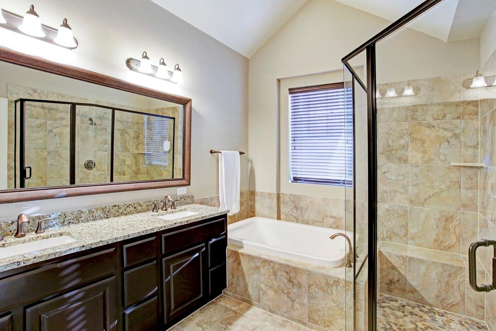 The handsome primary bathroom. Large, glass walk-in shower, tub, dual sinks, decorative mirror and plenty of counter space.
