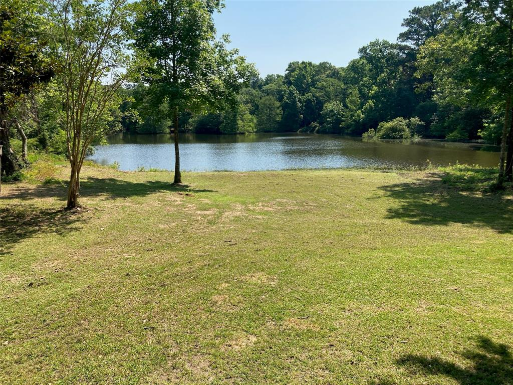 Need a private place in the country on 25 acres with your own private lake to get away. This is what you're looking for just 60 miles from downtown Houston. Very private spot to build your home overlooking a beautiful six acre spring fed lake surrounded by trees. You can get in your lawn chair and enjoy some fishing, get in your kayak or small boat and explore the shores of the lake, or just sit and watch the birds and relax. Watch out for the gators! The mobile home needs some love but can soon become your next Sportsman's Shack. Must see to appreciate the privacy!  Although this home is within a floodplain, there is no record of flooding since 1970.