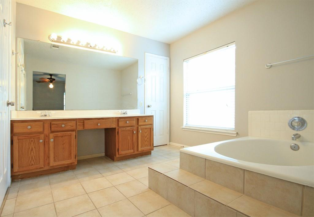 The primary bath features dual vanities and separate tub and shower.