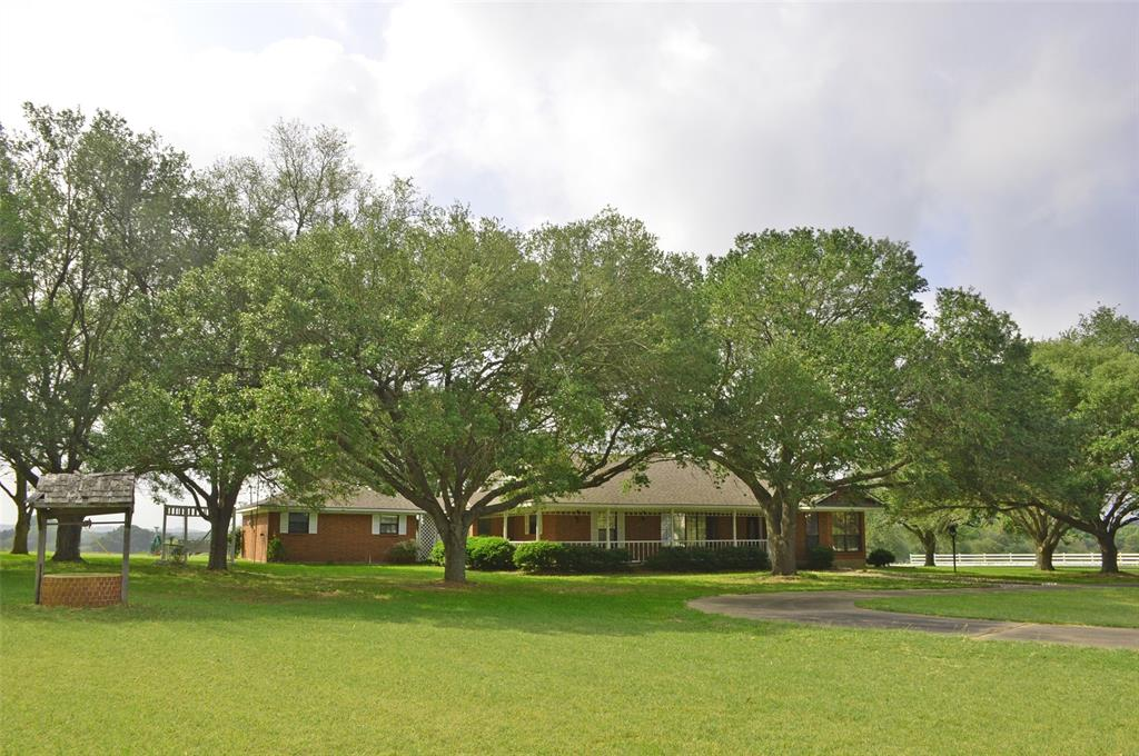 This is a fabulous 4+ ac tract shaded by wonderful trees. Great elevation overlooking the neighbor's lake. 2,051 SF 3 bed 2.5 bath with 2 car garage attached by breezeway plus a detached 3 bay workshop. Patio and porches AND a gazebo. The kitchen has been upgraded with nice counters and tile flooring. The living room features wainscot block paneling, laminate floors and fireplace. Home needs additional updating, the garage has a half bath and could easily be converted into an additional living area.