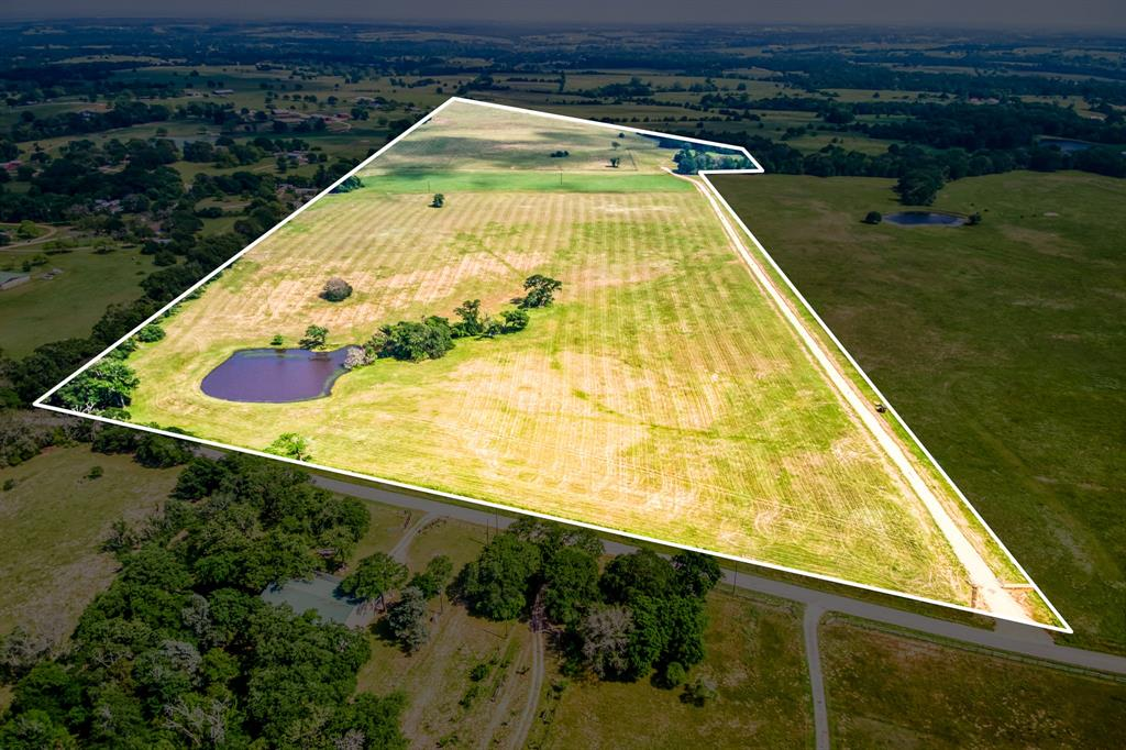 Look at this Beauty, 77.08 acres of rolling hills with endless views and only a little over 4 miles out of Brenham. Here is a great place to create your very own Farm or Ranch. The rolling hills offer numerous building sites which include one that over looks the nice size pond, that has never gone dry. There is a new entrance that leads down a newly constructed 18 ft. wide X 2000 plus ft. gravel driveway for easy access to the back part of the property. There is a coastal hay field, lots of native grasses, a few scattered trees and good exterior fences . Property is currently used for cattle grazing and making hay.  There is an active Agriculture Exemption held by a cattle lease. A Bluebonnet Electric line runs mid way through the property, in the hay field, which makes having electric access easy at any of the beautiful building locations. The property has community water available, Buyer to confirm. Seller will convey surface rights. Buyer's agent must make first contact.