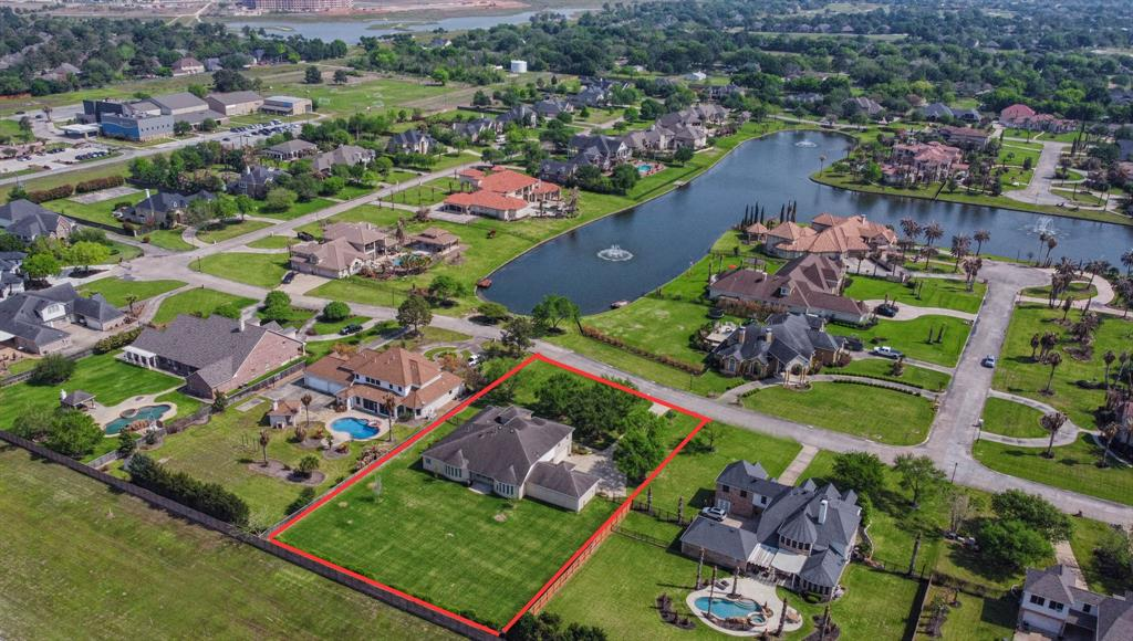 A Stately Custom one owner home located in a Manned Gated Subdivision in Katy known as Lake Pointe Estates. Curb appeal galore with Stone and Brick Façade, Stone Portico Entry, Plantation Shutters and 5 Car Garage, sitting on close to 1 acre of land with mature trees and water view, this home is sure to impress! The island kitchen features Stainless appliances, Granite counters, Hickory Cabinets, Built-in SS Refrigerator, loads of cabinets and plenty of counter space. High ceilings and built-ins flanking a beautiful fireplace beautify the den. The first floor study has built-in bookcases, one with a hide a room behind that can be used for extra storage. There are 4 bedrooms located on the first floor with a fifth bedroom with full bath located on the second floor that can be used as a second office if needed. Large private Master Suite complete with Whirlpool tub, large closet and door to outside patio. Back yard is large and a blank slate ready for the new owners to make their own!