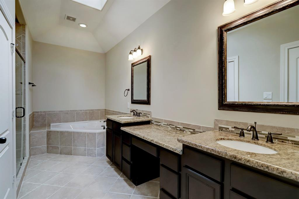 The primary bath with granite includes dual sinks as well as a vanity space, private water closet (door on the far left of the photo), frame-less glass enclosed shower stall and separate jetted tub. You can just see the corner of the ceiling skylight providing excellent natural light during the day.