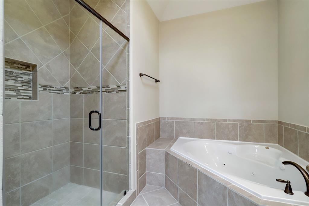 The shower stall is roomy and includes a built-in shelf.