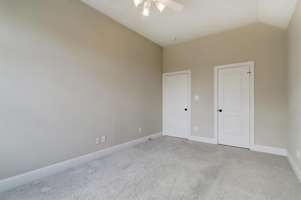 A mirror of the other secondary bedroom, door to the hall on the left and to the walk-in closet to the right.