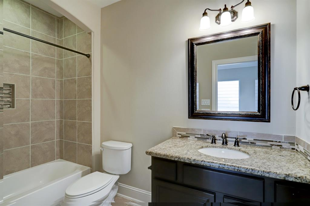 Just steps from both secondary bedrooms is this gorgeous full bath with a shower/tub combo (and same as the primary bath a built-in shelf for supplies).