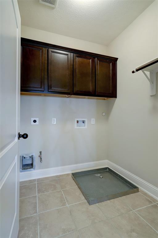 The final interior space is this big utility/laundry room located just outside the primary suite. There are gas and electric connections for a dryer, as well as a drain and pan for the washer.